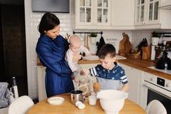 Familia feliz que cuece junto en cocina blanca moderna Hija de la madre, del hijo y del bebé que cocina por mañana acogedora del  Fotos de archivo libres de regalías