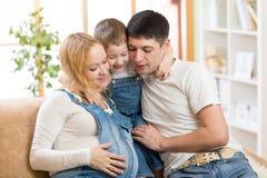 Familia feliz que cuenta con al bebé Mujer embarazada con fotografía de archivo libre de regalías