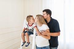 Familia feliz que cuenta con al nuevo bebé Beso de la mujer embarazada el pequeño hijo Fotografía de archivo libre de regalías