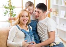 Familia feliz que cuenta con al nuevo bebé Mujer embarazada fotografía de archivo libre de regalías