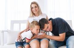 Familia feliz que cuenta con al nuevo bebé Mujer embarazada con el marido y el pequeño hijo Foto de archivo libre de regalías