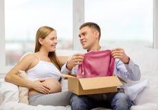 Familia feliz que cuenta con la caja del paquete de la abertura del niño Foto de archivo