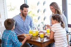 Familia feliz que desayuna junto Foto de archivo
