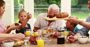 Familia feliz que desayuna junto almacen de video