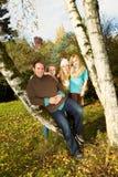 Familia feliz que descansa al aire libre durante un día agradable en temporada de otoño Imágenes de archivo libres de regalías