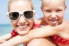 Familia feliz que descansa en la playa en verano imágenes de archivo libres de regalías