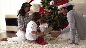 Familia feliz que descubre los regalos el día de la Navidad almacen de video