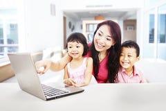 Familia feliz que disfruta de la hospitalidad en la computadora portátil Imagen de archivo