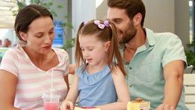 Familia feliz que disfruta del almuerzo en un restaurante almacen de video
