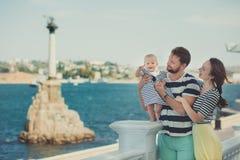 Familia feliz que disfruta junto del tiempo hermoso de la vida que lleva la madre morena de la ropa del padre joven colorido suav fotos de archivo libres de regalías