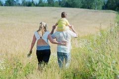 Familia feliz que entra en el campo fotografía de archivo libre de regalías