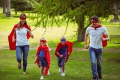 Familia feliz que finge ser funcionamiento del super héroe Fotografía de archivo libre de regalías