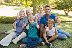 Familia feliz que gesticula los pulgares para arriba en el parque Foto de archivo libre de regalías