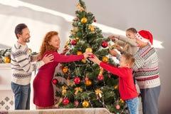 Familia feliz que goza de la decoración del árbol del día de fiesta Foto de archivo