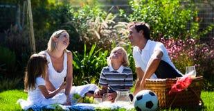 Familia feliz que goza del sol en una comida campestre Imagen de archivo