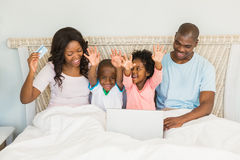 Familia feliz que hace compras en línea con el ordenador portátil Fotografía de archivo libre de regalías