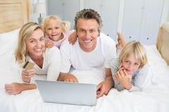 Familia feliz que hace compras en línea en el ordenador portátil en el cuarto de la cama imagenes de archivo