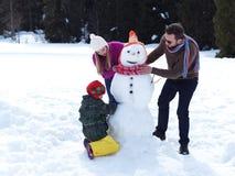 Familia feliz que hace el muñeco de nieve foto de archivo libre de regalías