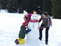 Familia feliz que hace el muñeco de nieve imagen de archivo