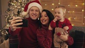 Familia feliz que hace el selfie en casa en el fondo del árbol de navidad Concepto de la celebración de la Navidad del Año Nuevo  almacen de video