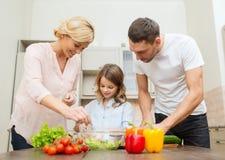 Familia feliz que hace la cena en cocina Imagenes de archivo