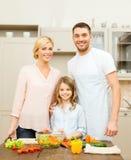 Familia feliz que hace la cena en cocina Foto de archivo