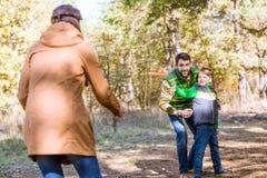 Familia feliz que juega con el disco volador imagenes de archivo