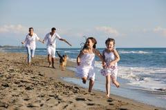 Familia feliz que juega con el perro en la playa Foto de archivo libre de regalías