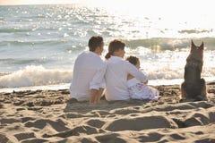 Familia feliz que juega con el perro en la playa Imagen de archivo libre de regalías