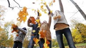 Familia feliz que juega con las hojas de otoño en parque metrajes