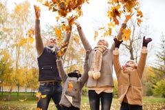 Familia feliz que juega con las hojas de otoño en parque Fotografía de archivo