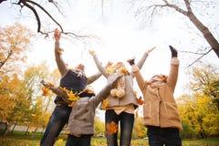 Familia feliz que juega con las hojas de otoño en parque Fotografía de archivo libre de regalías