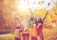 Familia feliz que juega con las hojas de otoño en parque Imagen de archivo libre de regalías