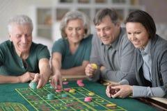 Familia feliz que juega con los microprocesadores del casino imagenes de archivo