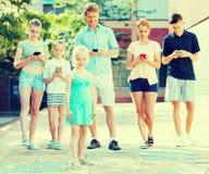 Familia feliz que juega con los teléfonos móviles Fotografía de archivo libre de regalías