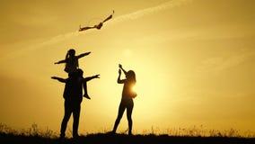 Familia feliz que juega con una cometa mientras que en el prado, puesta del sol, en d?a de verano Tiempo divertido de la familia  metrajes