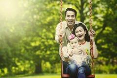 Familia feliz que juega el oscilación en el parque Fotos de archivo libres de regalías