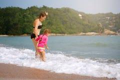 Familia feliz que juega en agua azul en un centro turístico tropical en el s fotografía de archivo