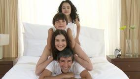 Familia feliz que juega en cama junto almacen de metraje de vídeo