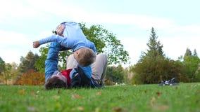 Familia feliz que juega en el césped Un padre cariñoso joven aumentó el alto del niño sobre su cabeza, las sonrisas del niño cont metrajes