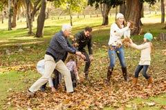 Familia feliz que juega en el parque junto foto de archivo