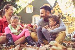 Familia feliz que juega en el patio trasero, estación del otoño imagen de archivo libre de regalías