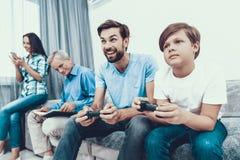 Familia feliz que juega en la consola junto en casa fotografía de archivo