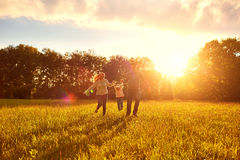 Familia feliz que juega en la hierba en el parque por la tarde Imagen de archivo