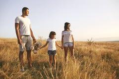 Familia feliz que juega en la naturaleza en verano en la puesta del sol fotografía de archivo