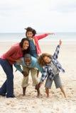 Familia feliz que juega en la playa foto de archivo libre de regalías