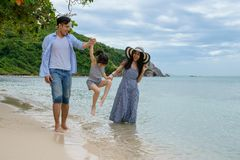 Familia feliz que juega en la playa en el tiempo del día Imágenes de archivo libres de regalías