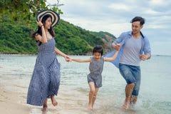 Familia feliz que juega en la playa en el tiempo del día Foto de archivo