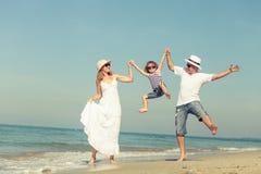 Familia feliz que juega en la playa en el tiempo del día fotos de archivo