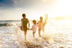 Familia feliz que juega en la playa en la puesta del sol fotografía de archivo libre de regalías